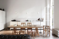 04 The kitchen and dining space are united in one, with white cabinets and light-colored wooden dining set