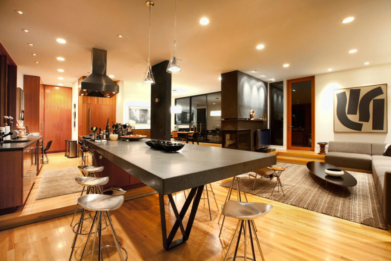The kitchen features a large concrete kitchen island and a breakfast table at the same time