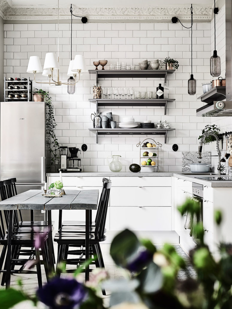The kitchen is clad with simple white tiles, there are white cabinets and open metal shelves