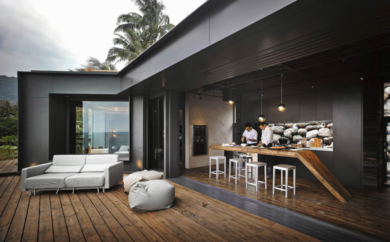 The kitchen is minimalist and dark and it can be opened to the outdoors easily