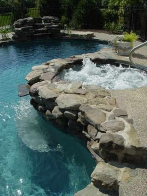 a hot tub covered with riverstone to separate it from a kidney-shaped pool