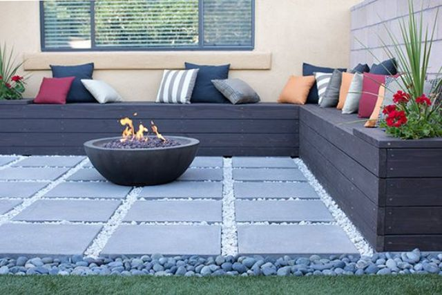 dark pallet bench with storage and a fire pit on a stone tile deck