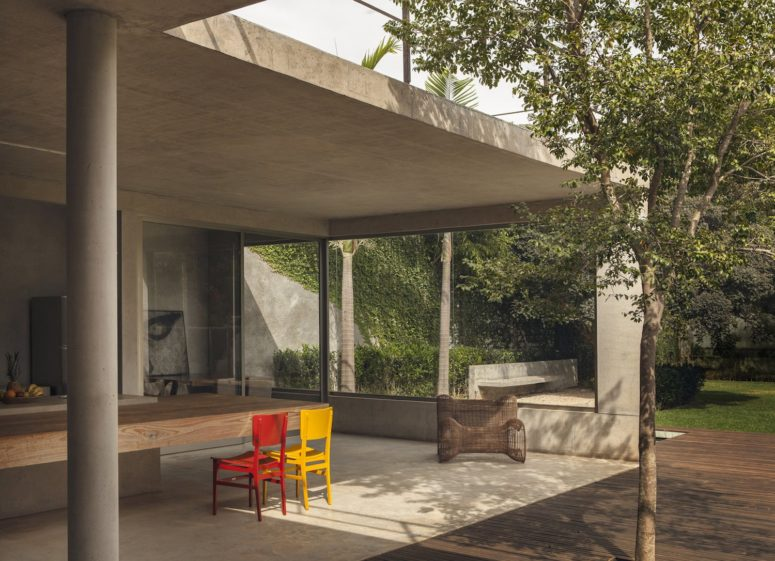 Here you'll see an outdoor dining space with a thick dining table and colorful chairs and floor-to-ceiling windows
