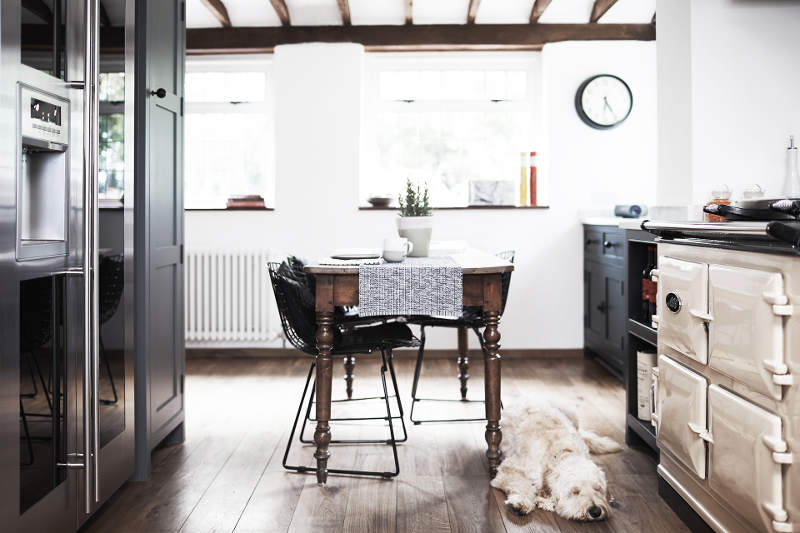 The hearth is an old fashioned one, and the dining table is a wooden one with carved legs