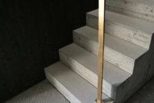 05 The staircase is concrete. with minimalist brass rails