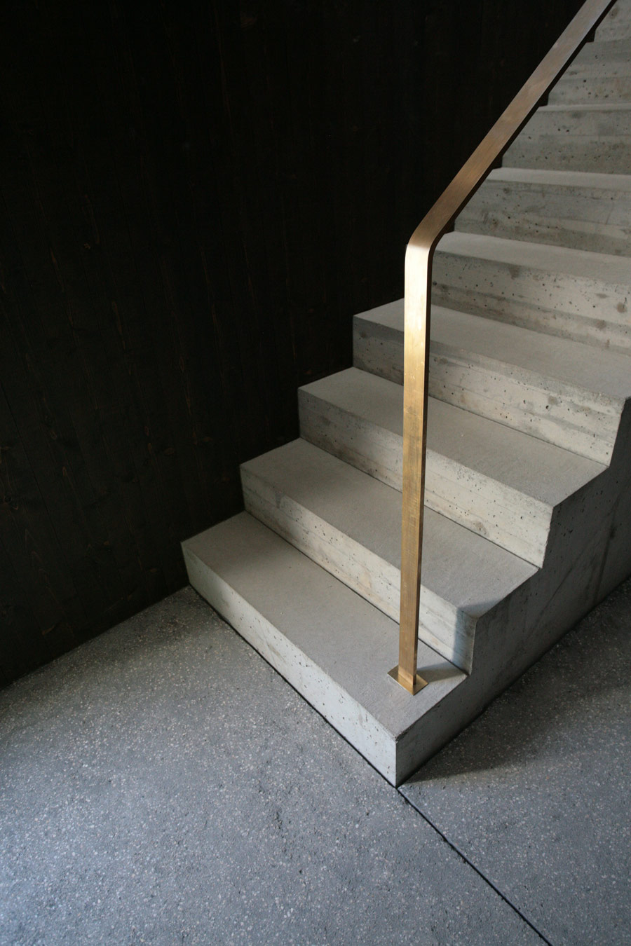 The staircase is concrete. with minimalist brass rails