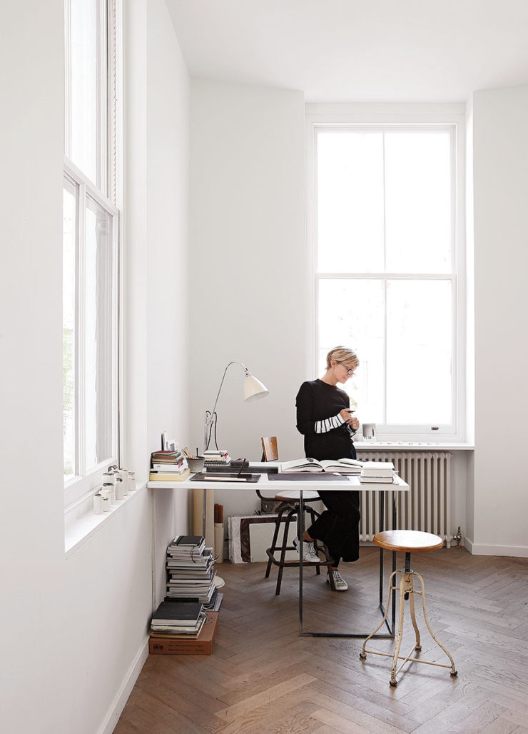 This is the workspace of the designer, with a wall-mounted desk and vintage stools