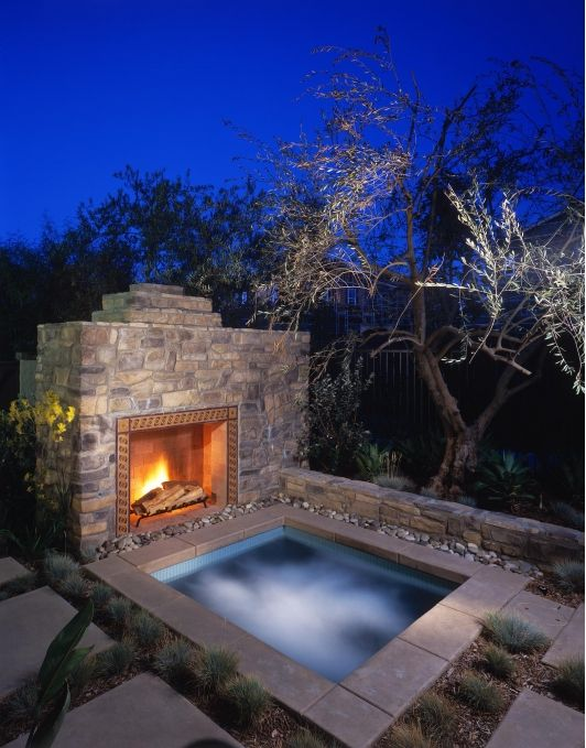 sunken jacuzzi clad with stone and with a fireplace in front of it for more comfort