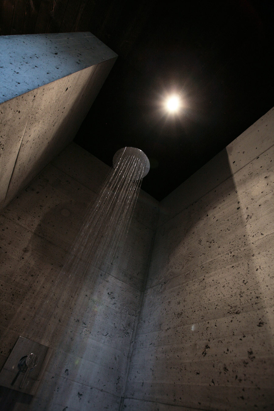 The bathroom is also industrial, of rough concrete, and there's only a shower