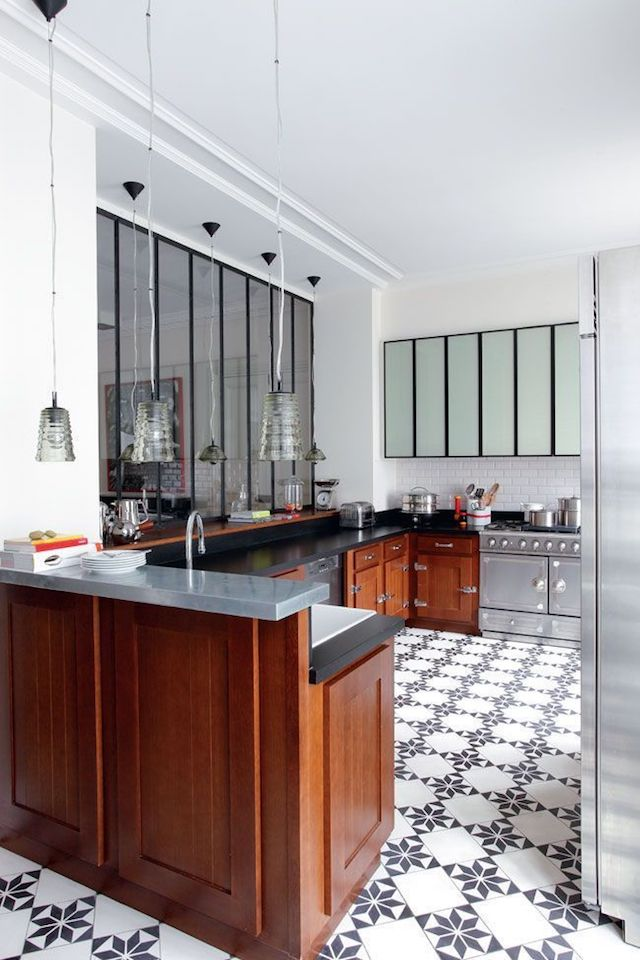 The kitchen is eclectic with warm-colored cabinets and stainless steel appliances