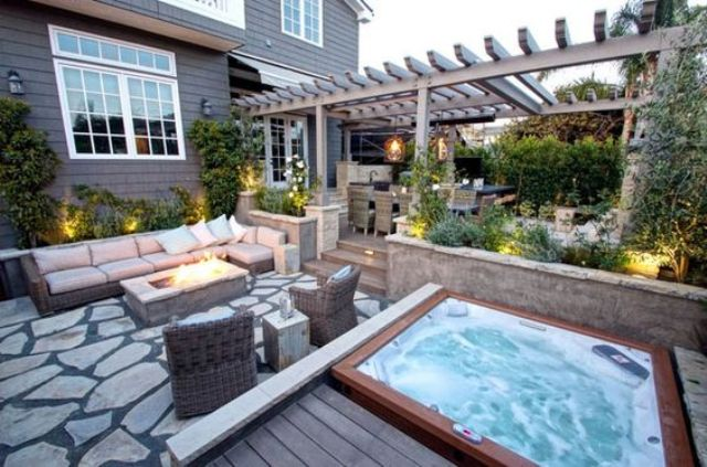 an outdoor living room with a fire pit and a jacuzzi on a wooden deck
