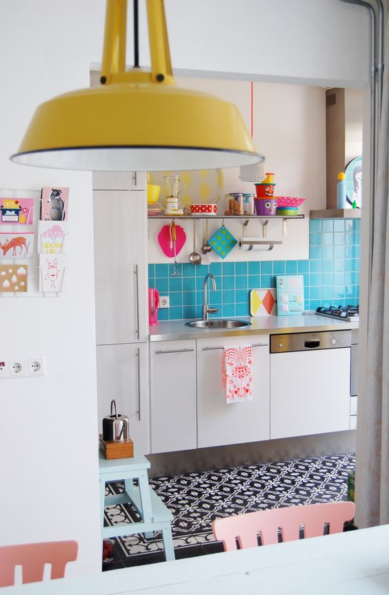 a bold light blue tile kitchen backspalsh and colorful dishes