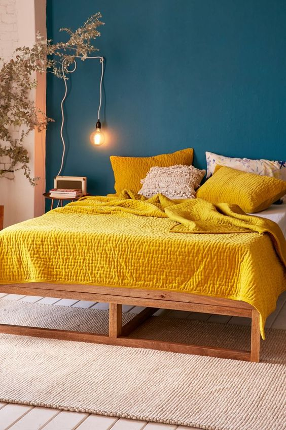 a navy statement wall contrasts with sunny yellow bedding