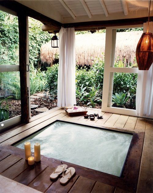 a sunken jacuzzi in a pavilion with glass doors for cases of bad weather
