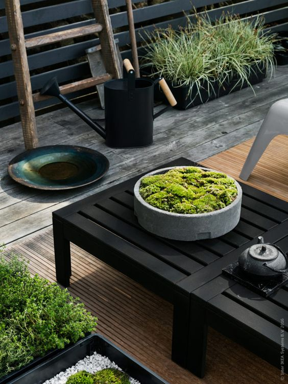 black Applaro furniture on brown decking with a moss arrangement makes the space Japanese-like