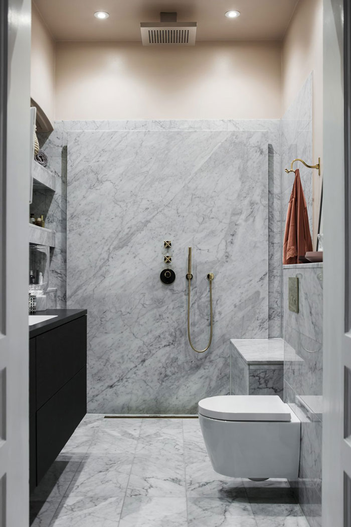The bathroom is small, clad with white marble and with brass fittings for a chic look