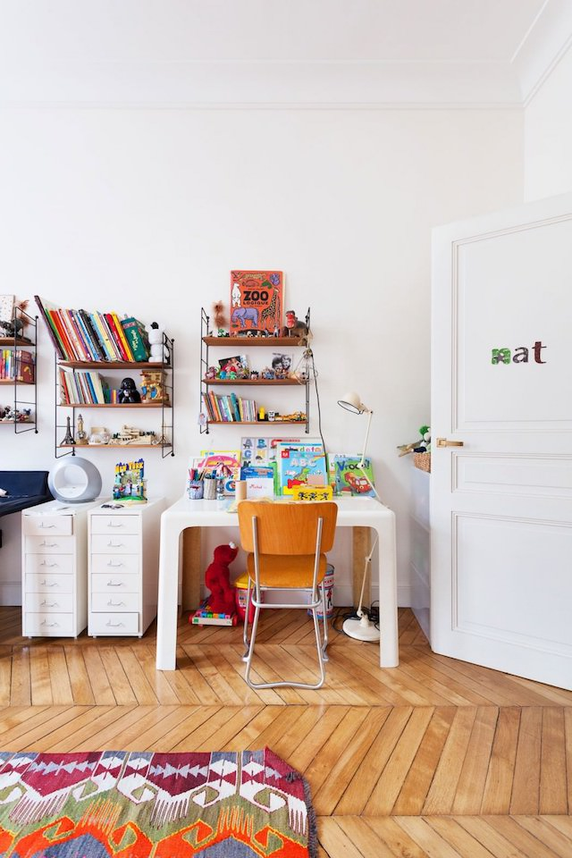 The kid's room is bright and colorful, with various pattern and comfy furniture