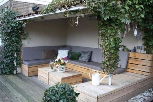 a deck with a large upholstered pallet bench and a matching pallet table