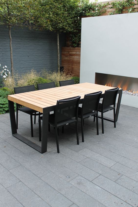 a minimalist table with black emtal legs and light-colored wooden tabletop