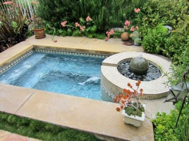 garden jacuzzi clad with stone tiles with greenery around