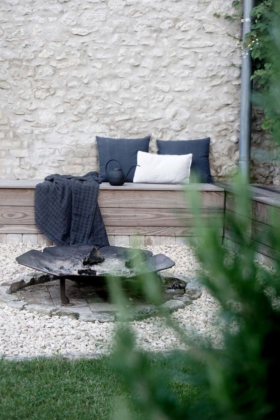 wooden L-shaped bench, a metal fire pit look Nordic and laconic