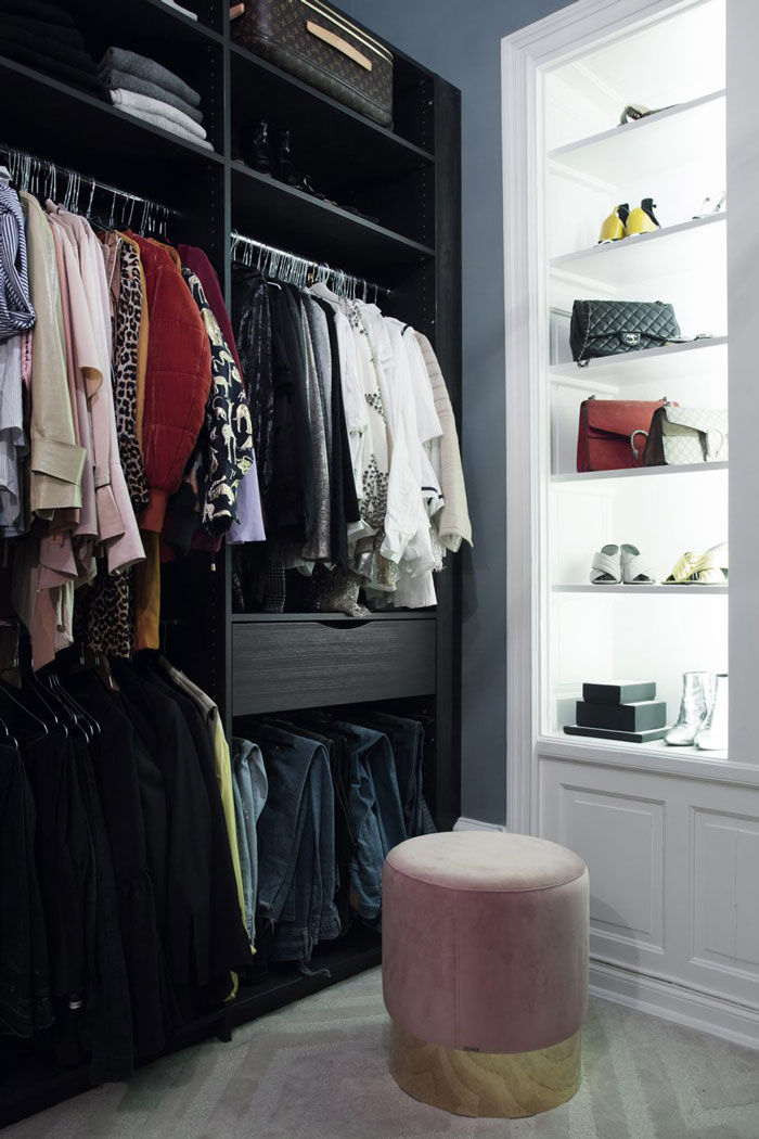 The closet is small and comfy, the wardrobe is opened and there are lit up shelves