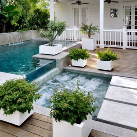 a jacuzzi next to the outdoor pool with a waterfall and a wooden deck