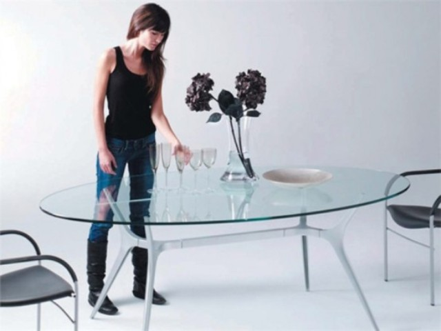an oval glass top with unique spider-inspired legs that make it eye-catching