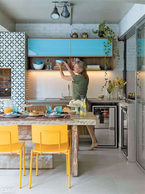 bold blue cabinets and sunny yellow chairs for an eye-catchy space