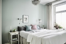 11 The master bedroom features green walls, a large crystal chandelier and soft textiles