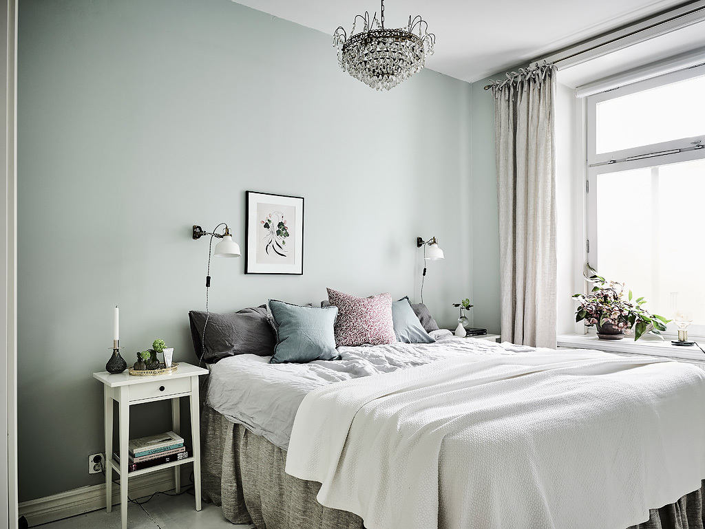 The master bedroom features green walls, a large crystal chandelier and soft textiles