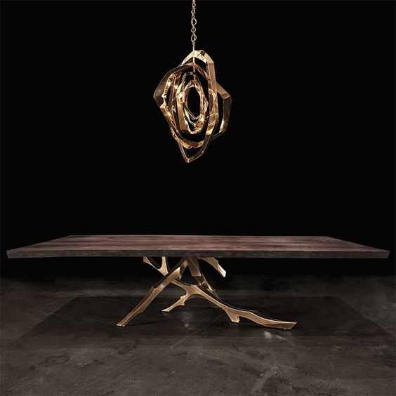 a dark stained table with bronze branch legs and a matching pendant