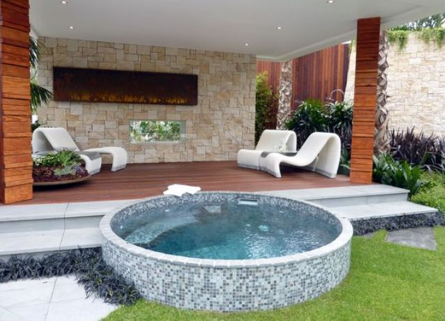 a round jacuzzi clad with small blue tiles in front of a deck
