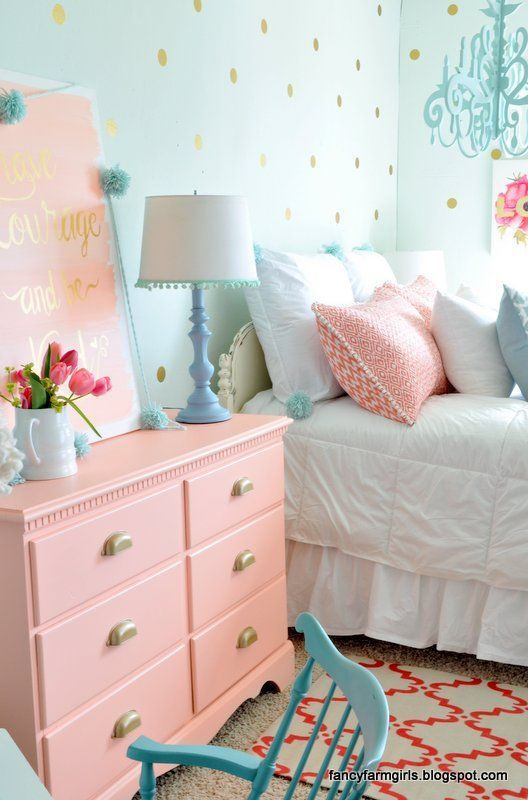 a salmon pink dress, pillows and an artwork are ideal for this cozy bedroom