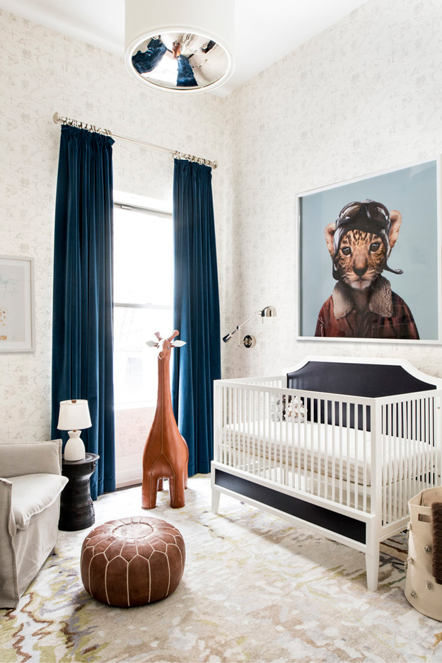 Even the stylish kid's room features a cool artwork and a leather giraffe