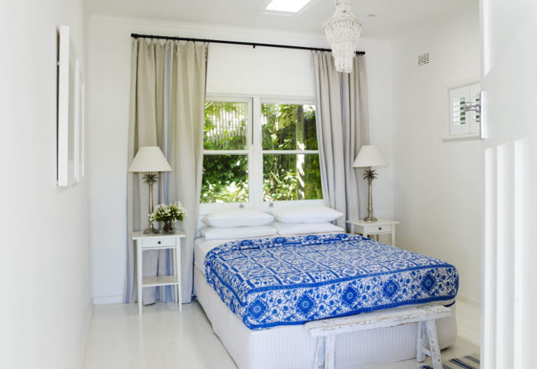 The second bedroom is all-white with a bold patterned bedspread