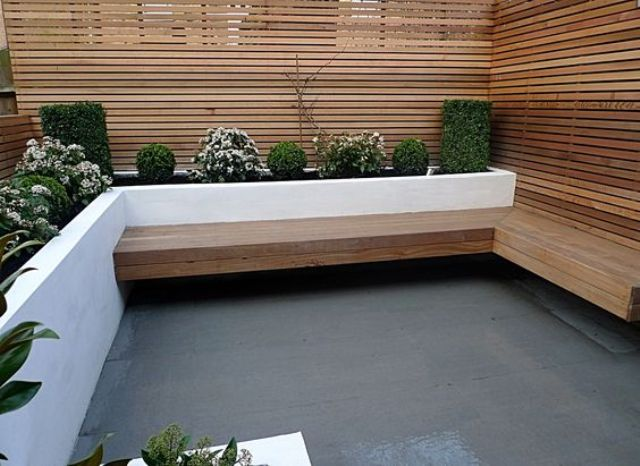 a cozy wind-sheltered area with a bench and a white modern planter