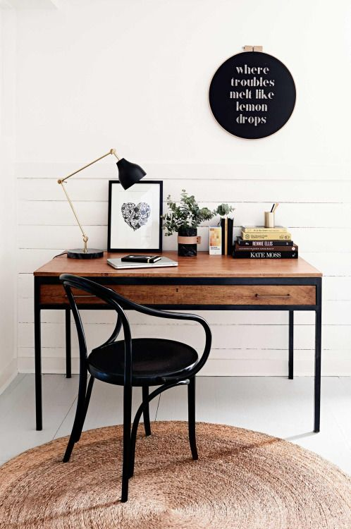 a modern desk in black framing and with stained wood