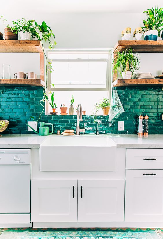 a brick backsplash painted in emerald color echoes with greenery