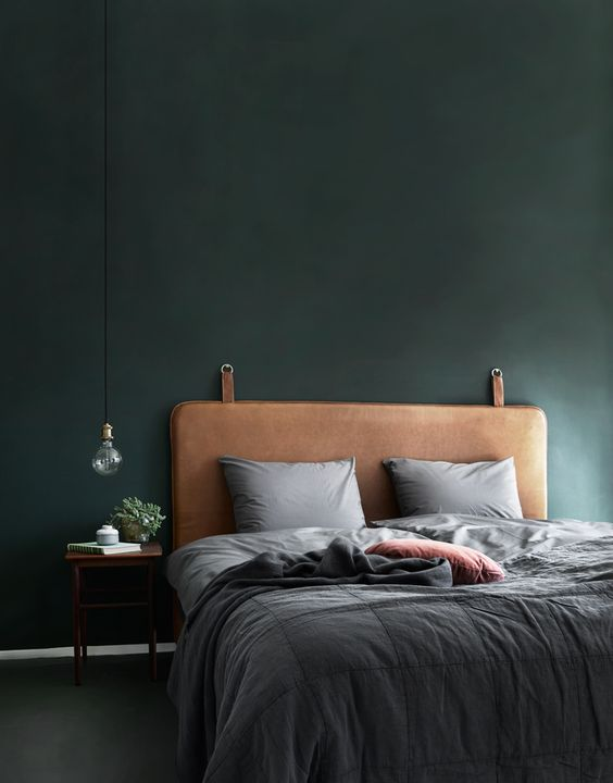a brown leather upholstered bed with a dark green wall create a manly feel