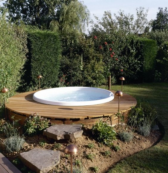 a round wooden deck with a jacuzzi and green walls all around to keep privacy