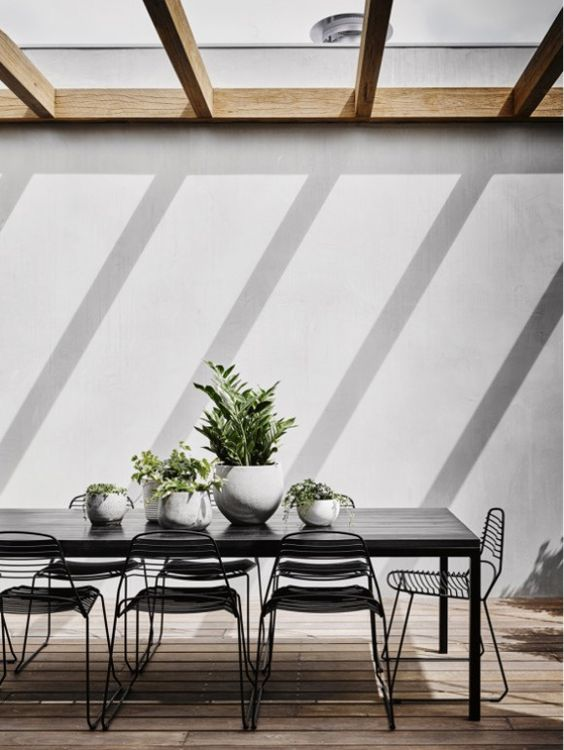 black dining table and black metal chairs for a chic modern terrace