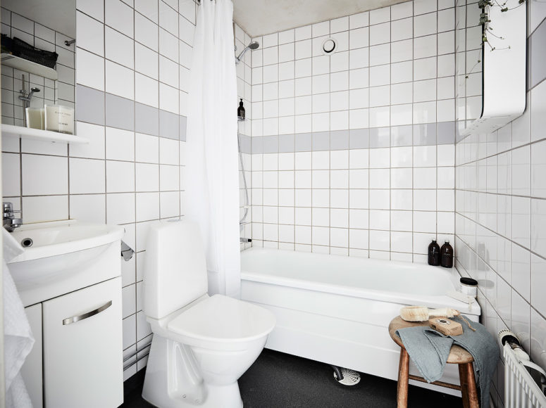 The bathroom is done in white and grey tiles, and a wooden stool adds texture