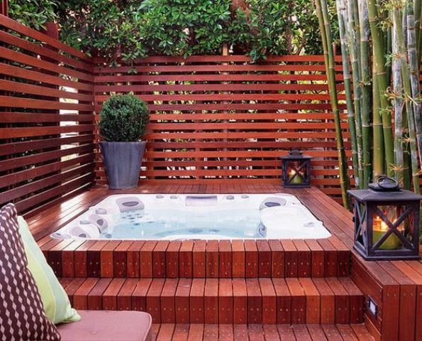 a wood clad jacuzzi with a plank wall around and lanterns and greenery in pots