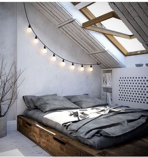 a reclaimed stained wooden bed with drawers gives the attic bedroom a barn feel