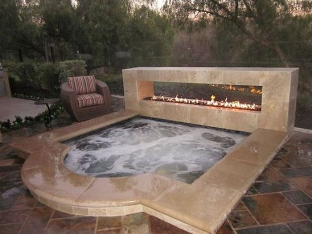 a sunken jacuzzi with a stone edge and a fireplace next to it for a dramatic look