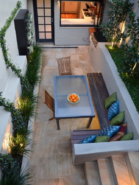 a small patio with a stained wooden L-shaped bench and a modern glass table