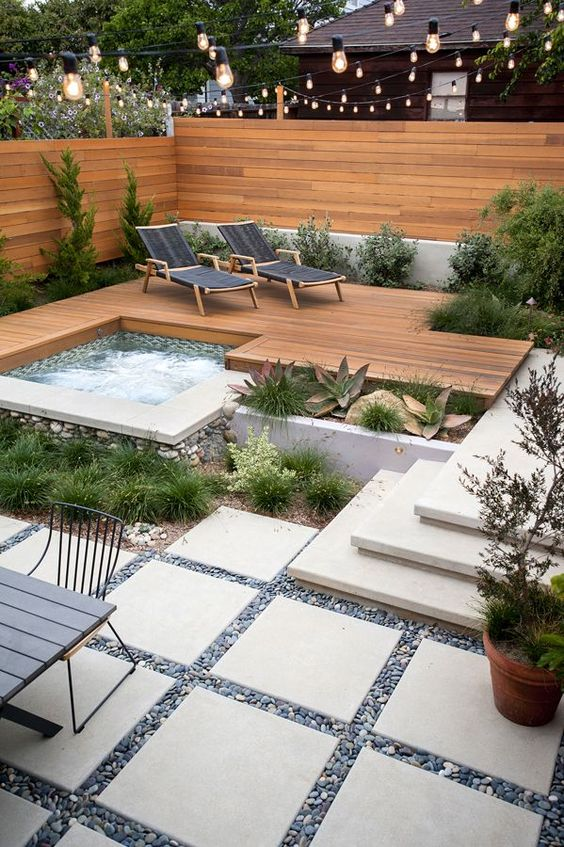 a wood deck with loungers and a jacuzzi surrounded with succulents