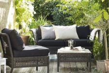 18 Kungsholmen lounge set with black upholstery contrasts with greenery around