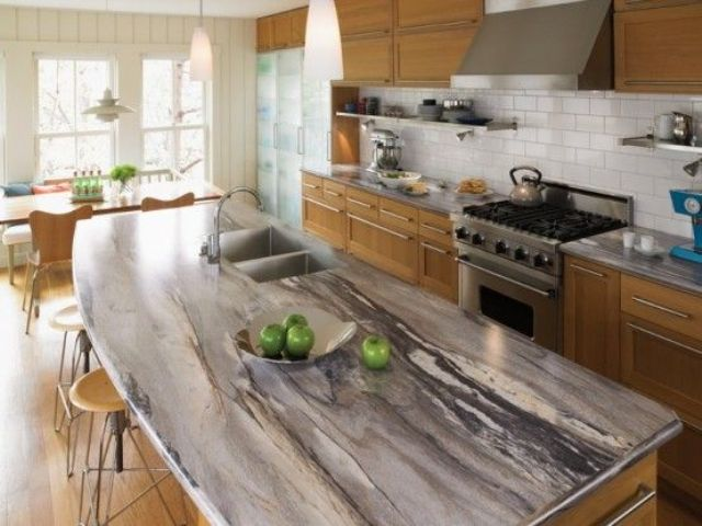 a chic granite counter contrasts with warm-colored cabinets of wood